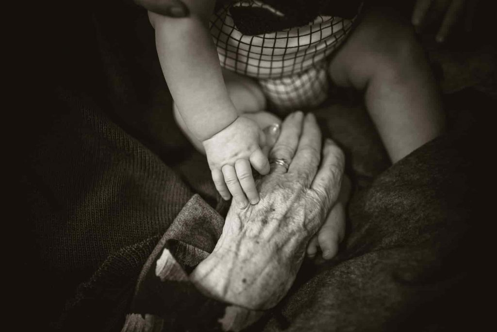 Old hand holding young hand by Rod Long